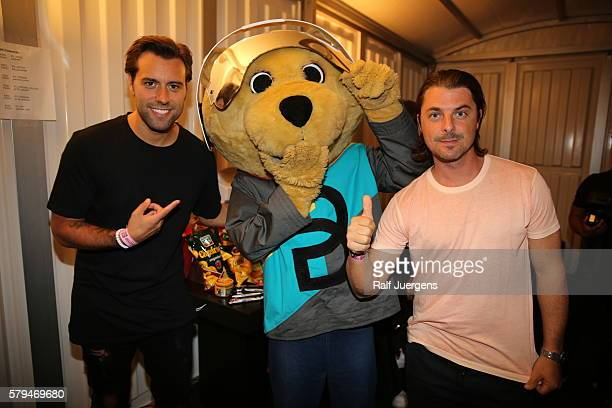 Axwell BreuniBaer mascot of Breuninger and Sebastian Ingrosso pose for a photograph at the ParookaVille Festival on July 15 2016 in Weeze Germany