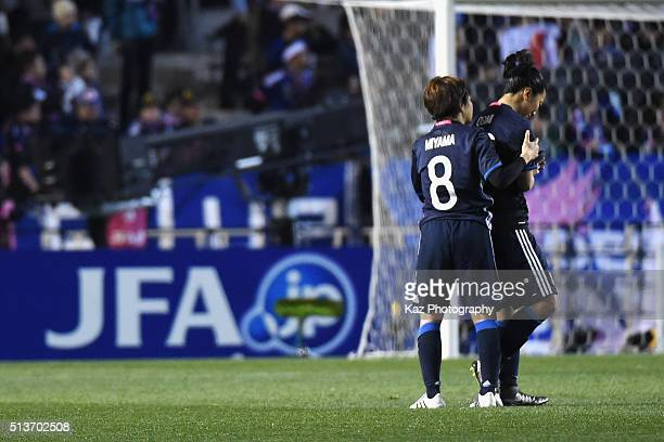 Aya Miyama of Japan consoles her team mate Yuki Ogimi after their 1-2 defeat in the AFC Women's Olympic Final Qualification Round match between Japan...