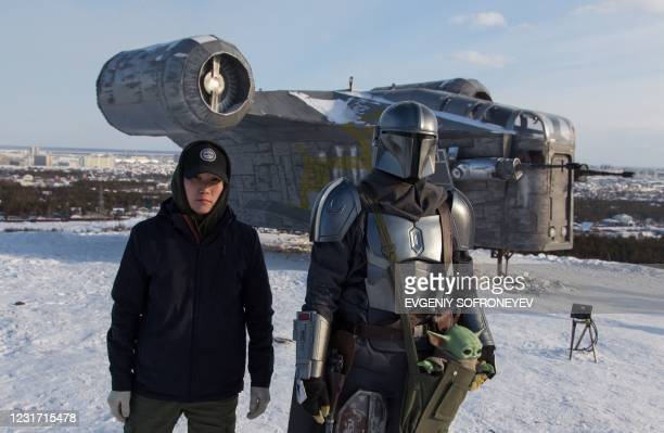 Ayaal Fyodorov one of the designers poses with a man wearing a costume of the StarWars protagonist Din Djarin in front of a giant replica of the...