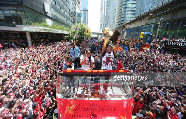 TORONTO ON JUNE 17 Ayahna CornishLowry waves flags as her husband Toronto Raptors guard Kyle Lowry hoists the Larry O'Brien NBA Championship Trophy...