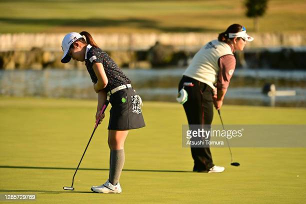 Ayaka Furue and Miki Sakai of Japan prepare for their putts on the 18th green on the play-off second hole during the final round of the Ito-En Ladies...