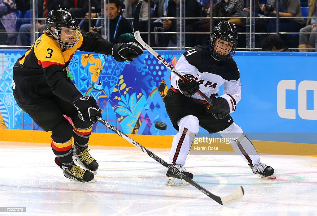 Ayaka Toko #4 of Japan passes the puck against Sophie Kratzer #3 of Germany in the first period during the Women's Classifications Game on day 11 of the Sochi 2014 Winter Olympics at Shayba Arena on February 18, 2014 in Sochi, Russia.