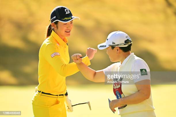 Ayaka Watanabe of Japan and Jiyai Shin of South Korea elbow bump after holing out on the 9th green during the first round of the Daio Paper Elleair...