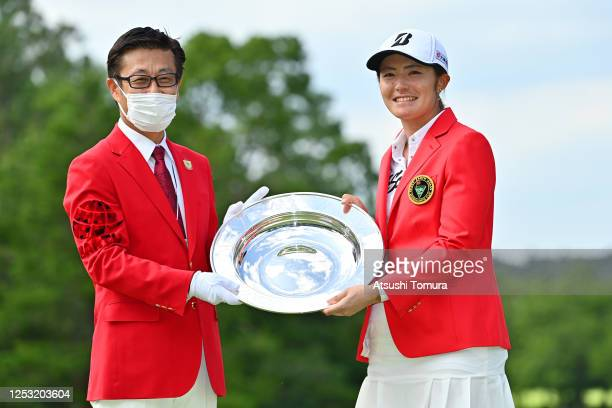 Ayaka Watanabe of Japan is presented the trophy by Earth Corporation Chairman Tatsuya Otsuka during the award ceremony during the final round of the...