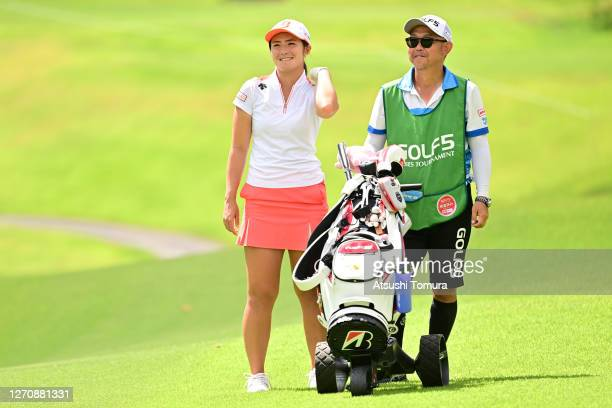Ayaka Watanabe of Japan talks with her caddie before her second shot on the 7th hole during the final round of the GOLF5 Ladies Tournament at the...