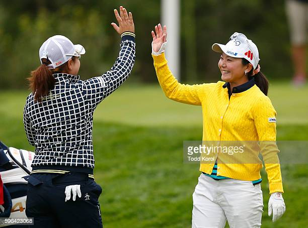 Ayako Uehara of Japan gets a high five from Mika Miyazato of Japan after getting a hole in one on the 11th hole during the third round of the...