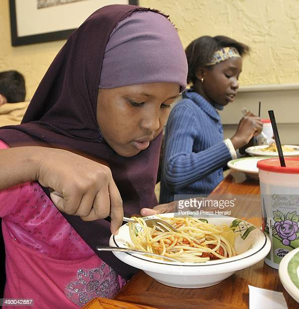 Ayan Mohamed stirs sauce into her spaghetti at the Olive Garden restaurant in South Portland as part of a learning project