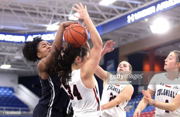Ayanna Townsend of the Xavier Musketeers gets into a scrabble with Holly Forbes of the Robert Morris Colonials during the second half at the UPMC...