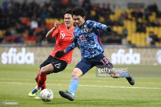 Ayase Ueda of Japan competes for the ball wuth Kim YoungGwon of South Korea during the EAFF E1 Football Championship match between South Korea and...