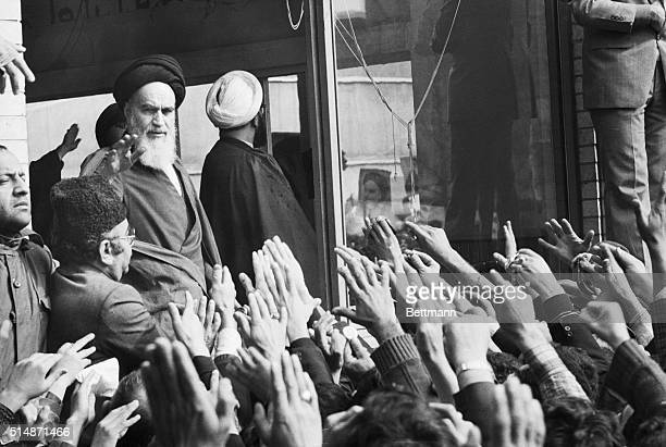 Ayatollah Khomeini waves to a crowd of supporters from the window of his Tehran home