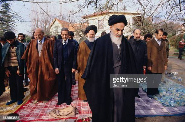 Ayatollah Ruhollah Khomeini and members of his suite seen during 12/7 prayer in his villa garden Khomeini said The Shah's train ride is coming to an...