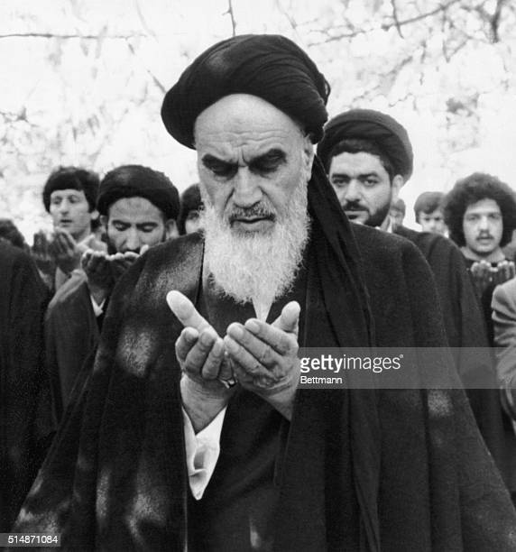 Ayatollah Ruhollah Khomeini prays in the garden of his villa in Pontchartrain near Paris where he is staying during his exile from Iran