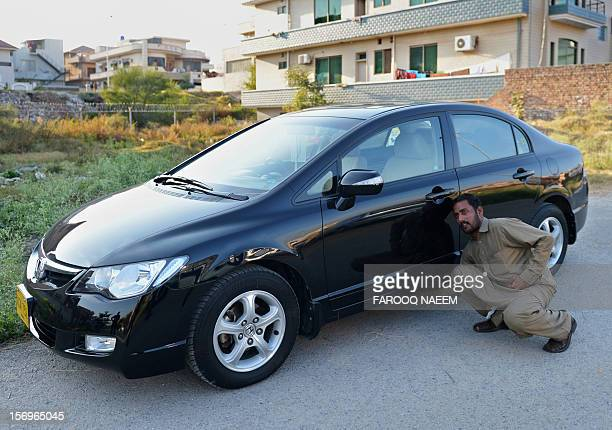 Ayaz driver of journalist and television anchor Hamid Mir points out the place where a device in a metal box was hidden under the front passenger...