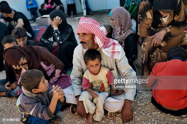 Ayed a Syrian refugee from Homs sits with two of his 7 children the morning after crossing into Jordan from Syria at the United Nations High...