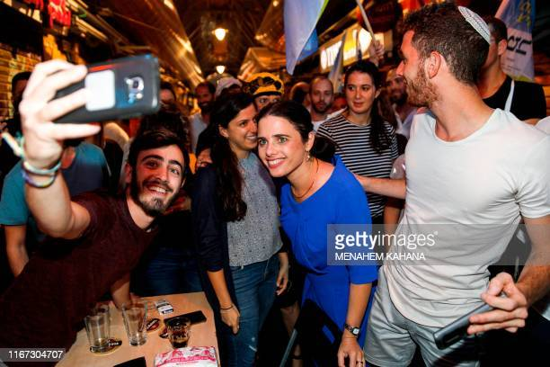Ayelet Shaked chairwoman of Israel's United Right party poses for a selfie picture with youths while on an election campaign tour at the Mahane...