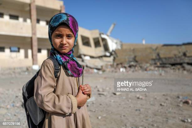 AYemeni school girl poses for a picture outside a school on March 16 that was damaged in an air strike in the southern Yemeni city of Taez The...