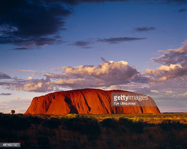 Ayers Rock Giant red rock formation at dusk overshadowed by storm clouds