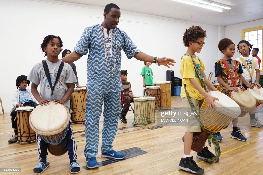 Ayinde (L), age 10, who is homeschooled by his mother Monica Utsey, takes part in an African drumming class as an extracurricular activity in Mount Rainier, Maryland on February 24, 2017. / AFP PHOTO / MANDEL NGAN / With AFP Story by Margaret