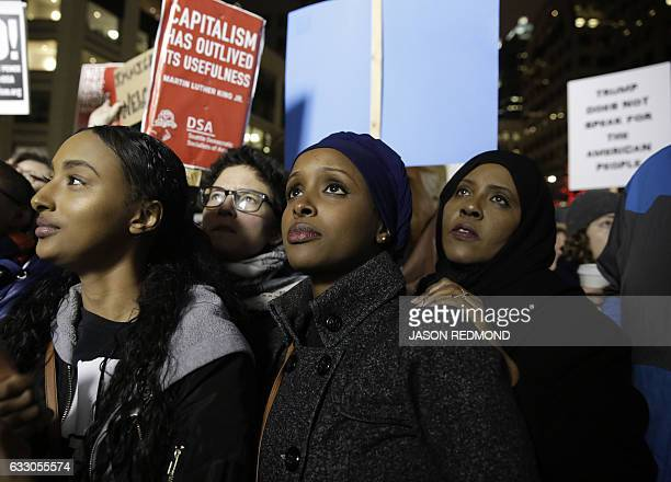Ayla Ali and her Somali refugee family members cousin Ryan Adem and aunt Maryan Farah listen to speakers at a rally for immigrants and refugees in...