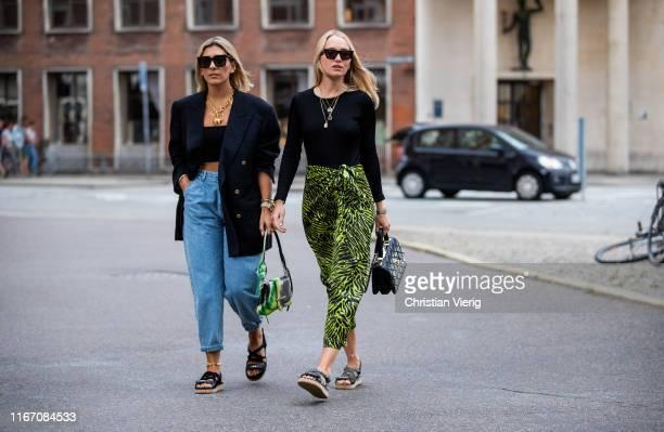 Aylin König is seen wearing denim jeans, cropped top, blazer, Prada bag, sandals and Juliane Diesner wearing skirt with jungle print outside Saks...