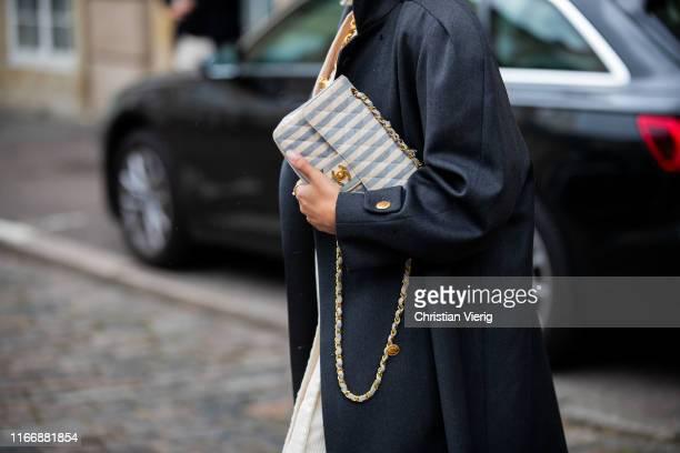 Aylin König seen wearing navy coat, striped Chanel bag outside Hofmann Copenhagen during Copenhagen Fashion Week Spring/Summer 2020 on August 08,...