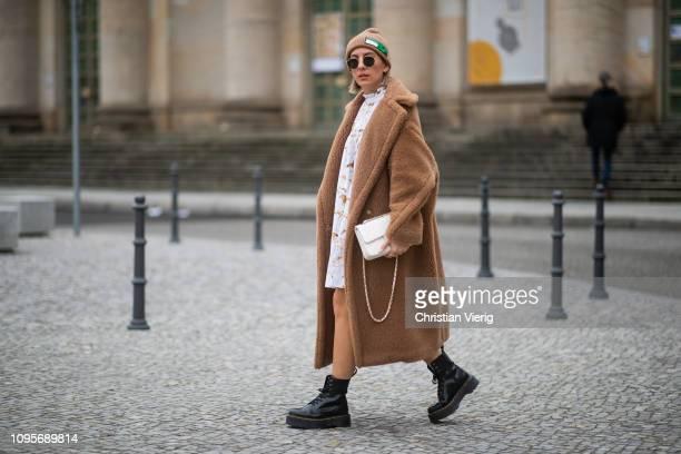 Aylin Koenig is seen wearing brown teddy coat Max Mara, white Ganni dress with print, Dr. Martens boots, white Chanel bag, Prada beanie during the...