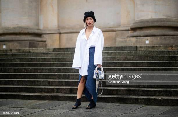 Aylin Koenig is seen wearing white oversized blouse Masion Margiela asymmetric navy blue skirt with slit Topshop black beanie Balenciaga ankle boots...