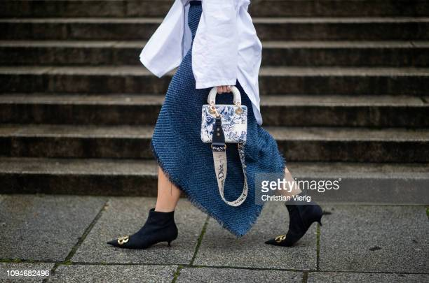 Aylin Koenig is seen wearing white oversized blouse Masion Margiela asymmetric navy blue skirt with slit Topshop Balenciaga ankle boots Dior bag...