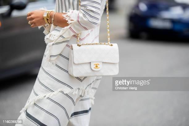 Aylin Koenig is seen wearing white striped dress, Chanel bag during Berlin Fashion Week on July 04, 2019 in Berlin, Germany.