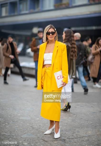 Aylin Koenig is seen wearing yellow blazer skirt white cropped top Celine clutch outside Max Mara on Day 2 Milan Fashion Week Autumn/Winter 2019/20...
