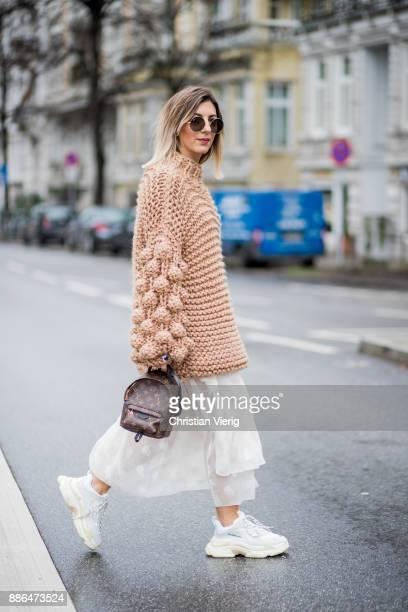 Aylin Koenig wearing a beige knit from Moms Handmade, white Balenciaga sneakers, mini Louis Vuitton backpack, white dress H&M Studio, round RayBan...