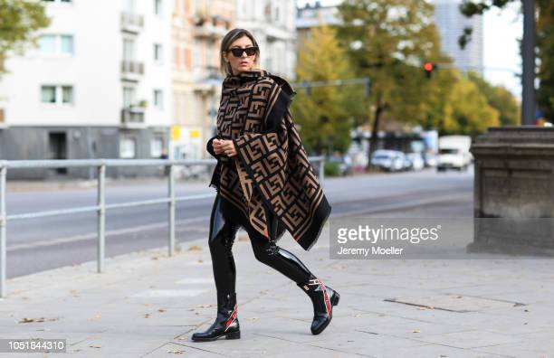 Aylin Koenig wearing a Jacquemus mini bag Fendi Poncho latex pants from topshop Dior boots Cartier jewelry and a Celine sunglasses on October 08 2018...