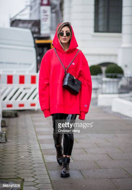 Aylin Koenig wearing a red oversized hoody Champions black Chanel mini bag black Asos pants Louis Vuitton boots round Ray Ban sunglasses on December...
