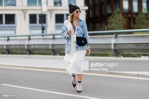 Aylin Koenig wearing Acne beanie denim jacket Prada bag white dress outside Versus Versace during London Fashion Week September 2017 on September 17...