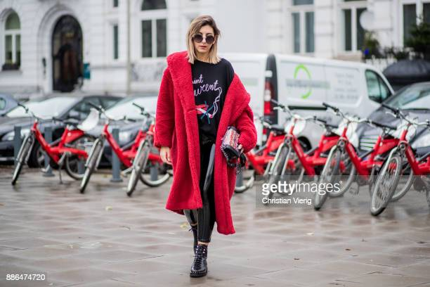 Aylin Koenig wearing black Valentino boots black pants Asos black tshirt Saint Laurent showing a print with lips and a crossed cigarette red Max Mara...