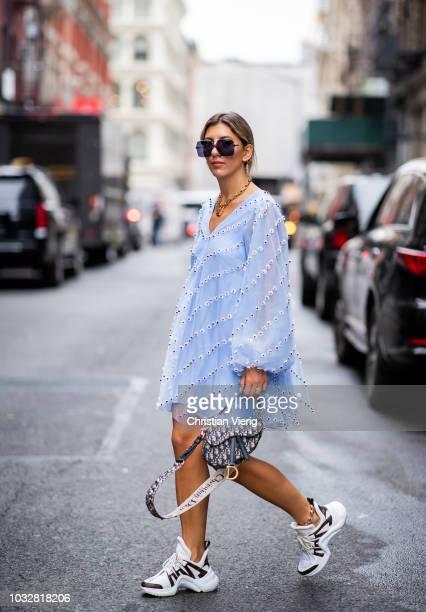 Aylin Koenig wearing blue dress Ganni sneaker Louis Vuitton Dior sunglasses bag necklace is seen during New York Fashion Week Spring/Summer 2019 on...