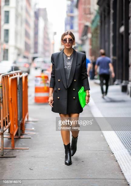 Aylin Koenig wearing boots Dior, Prada clutch, Balenciaga tshirt, Balmain blazer, Dior necklace, Dolce & Gabbana sunglasses is seen during New York...