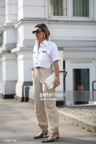 Aylin Koenig wearing Chanel logo blouse Dior sunglasses Balenciaga slippers Zara pants and statement earring Chanel bag and Cartier jewelry on April...