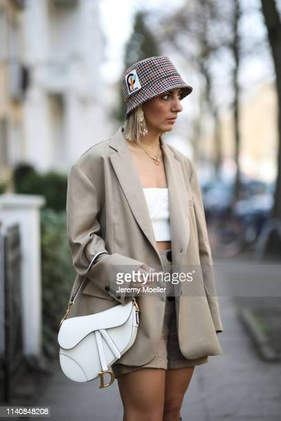 Aylin Koenig wearing Dior saddle bag in white Fendi boots Orseund Iris bra The Frankie Shop blazer Mango pants Prada hat and Cartier jewelry on April...
