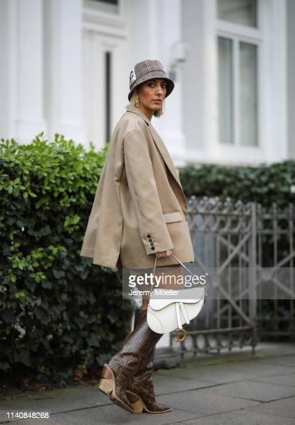 Aylin Koenig wearing Dior saddle bag in white Fendi boots Orseund Iris bra The Frankie Shop blazer Mango pants Prada hat and Cartier jewelry on April...