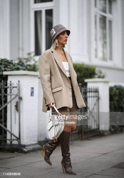 Aylin Koenig wearing Dior saddle bag in white, Fendi boots, Orseund Iris bra, The Frankie Shop blazer, Mango pants, Prada hat and Cartier jewelry on...