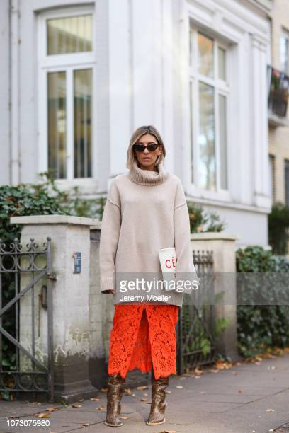 Aylin Koenig wearing Ganni skirt, H&M sweater, Fendi boots and Celine clutch on November 26, 2018 in Hamburg, Germany.