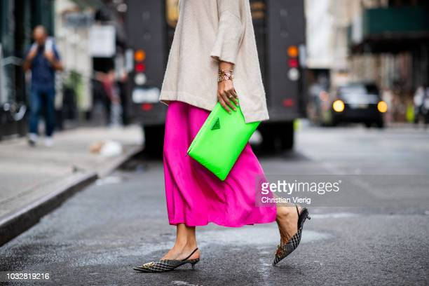 Aylin Koenig wearing neon pink dress HM Studio collection Prada neon clutch Dior necklace Dolce Gabbana sunglasses Mango knit seen during New York...