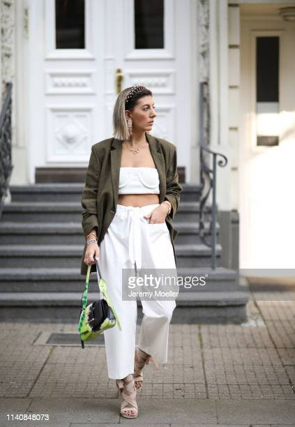 Aylin Koenig wearing Prada batik bag Christian Dior shoes Prada hairband Zara blazer Mango pants Orseund Iris bra and Cartier jewelry on April 06...