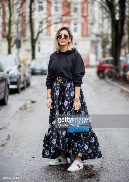 Aylin Koenig wearing white Gucci sneakers, blue Chanel bag, a navy dress with floral print H&M x Erdem, a black hoody Asos, black Gucci belt, Ray Ban...