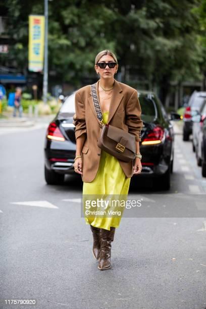Aylin Koenig wearing yellow dress brown bag Fendi blazer boots with print seen outside the Fendi show during Milan Fashion Week Spring/Summer 2020 on...
