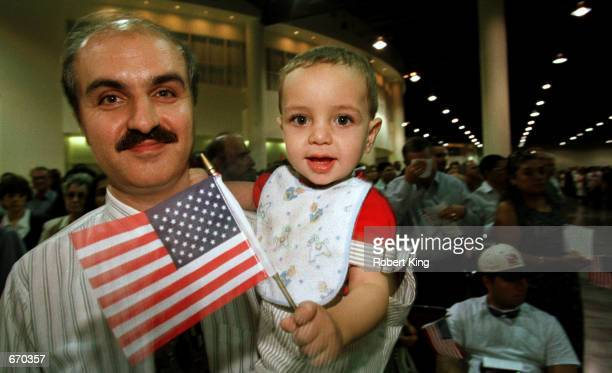 Ayman Sokkarie and his son Tariq of Lebanon celebrate after being officially being sworn in as American citizens in the Broward County Convention...