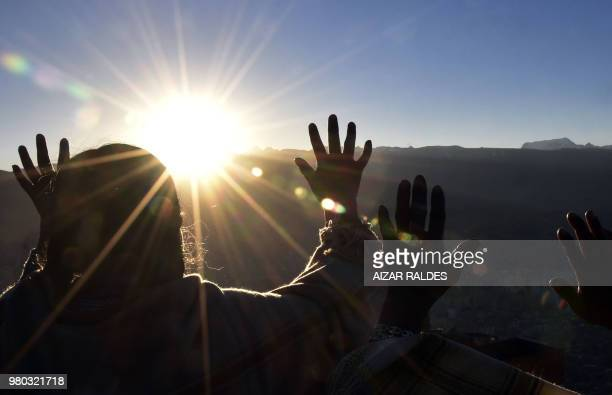 Aymara indigenous people raise their hands during a ritual at sunrise to celebrate the Aymara New Year on June 21 2018 at the Jacha Qullu viewpoint...