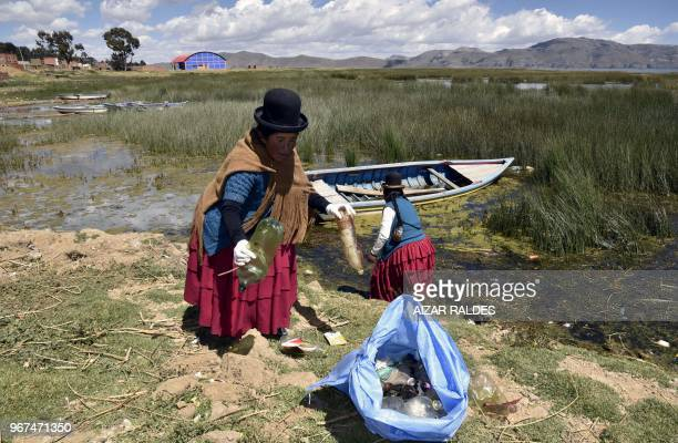 Aymara indigenous women clean the shore of the Titicaca lake in Puerto Perez La Paz department Bolivia on April 18 2018 A group of indigenous women...