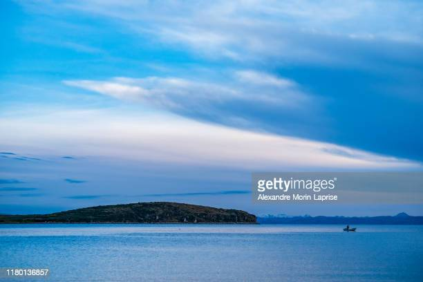 aymara man paddling and fishing in a small boat in the picturesque challa bay located in the famous sun island (isla del sol) - ボリビア ストックフォトと画像